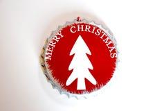 kapsylen dekorerade med glad jul som märker, och det vita trädet Arkivfoton