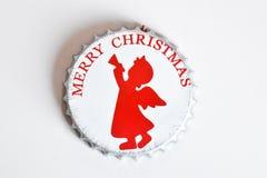 kapsylen dekorerade med glad jul som märker, och röd ängel Royaltyfria Foton