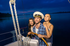 Kapten med flickor på yachten arkivbilder