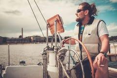 Kapten på en yacht bak styrninghjulet arkivbild