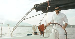 Kapten på yachten Den stiliga skäggiga mannen i vit kläder rymmer hans händer på ridningen för styrhjulet på yachten lager videofilmer