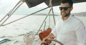 Kapten på yachten Den stiliga skäggiga mannen i vit kläder rymmer hans händer på ridningen för styrhjulet på yachten arkivfilmer