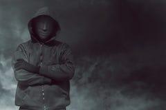 Kapturzasty mężczyzna z maskowy trwanie samotnym zdjęcie stock