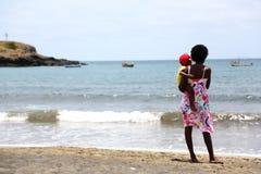 Kapverdisk kvinna med ett barn på stranden Arkivfoto