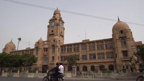 Karachi Municipal Corporation Building. Karachi Municipal Corporation KMC Building Side View at JInnah Road with Busy Traffic on a Cloudy Day stock footage