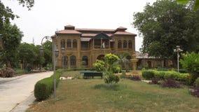 Karachi Quaid e Azam House Museum. Karachi Quaid e Azam Jinnah House Museum Side View with Garden and Waving Pakistan Flag on a Cloudy Day stock video