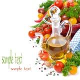Karaf met olijfolie, van kersentomaten en kruiden wordt geassorteerd dat Stock Foto
