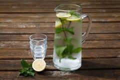 Karaf met water, munt en citroen Stock Foto