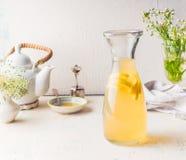 Karaff med den citrusa lemonaddrinken för vitt te på det vita köksbordet Sommardryckbegrepp royaltyfri fotografi
