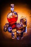 Karaff och två exponeringsglas med whisky och is Arkivfoto
