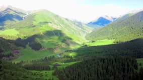 Karakol Glen Defile. Snow capped mountains forest with yurt camp and blue sky background clouds stock video