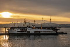Sunrise and city lines ferry at karakoy pier for passenger transport  in istanbul stock image