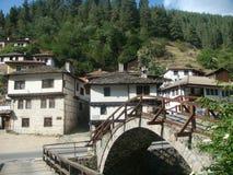 Karakteristiska hus av berget av nationalparken av Rhodopesen i Bulgarien med en liten bro av stenen arkivfoto