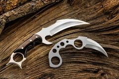 Karambit knives designer made, on the tree trunk. Karambit knife is very lethal weapon with a sharp and hooked blade. This kind of knives are better for hunt Royalty Free Stock Photo