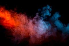 Karambol dwa strumienia dym z przemianą kolory błękit i czerwień przez pigment molekuł na czerni fotografia stock