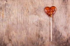 Karamell på en pinne på den gamla träbakgrunden Arkivfoto