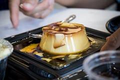 Karamellpudding i en svart maträtt. Arkivbild