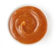 Karamellsoße im runden Teller auf weißem Hintergrund, Spitzenv Lizenzfreies Stockfoto