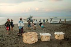 Karangasem, Бали, Индонезия Местные люди на песке черного пляжа вулканическом носят восхождение на борт поголовья паромом к проти
