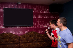 Karaoke. A man and teenage boy singing at karaoke club. Blank screen of the TV prompter Royalty Free Stock Photos
