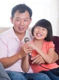 Karaoke asiático feliz do canto da família foto de stock royalty free