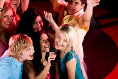 In karaoke bar. Portrait of happy people singing in microphone in the karaoke bar Stock Photography