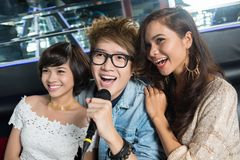 Karaoke bar. Happy young people enjoying themselves singing karaoke in the bar Royalty Free Stock Images