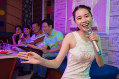 In karaoke bar. Portrait of a young girl singing in karaoke bar on the foreground Stock Images