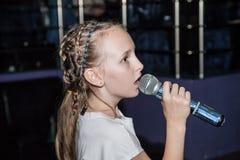 Karaoke del canto de la muchacha en un café fotografía de archivo libre de regalías