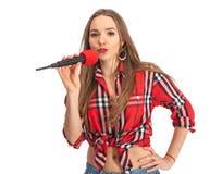 Karaoke del canto de la mujer con el micrófono Fotografía de archivo
