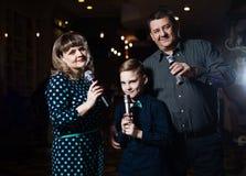 Karaoke della famiglia Ritratto di una famiglia felice, cantante in microfoni fotografia stock
