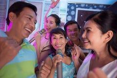 In karaoke with friends. Senior Vietnamese women singing in karaoke with her friends Royalty Free Stock Photos