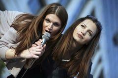 Karaoke fun. Two beautiful young females singing at a karaoke party Stock Image