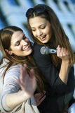Karaoke fun. Two beautiful young females singing at a karaoke party Stock Photography