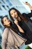 Karaoke fun. Two beautiful young females singing at a karaoke party Royalty Free Stock Photo