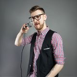 Karaoke man sings the song to microphone, singer with beard on g. Rey background. Funny man in glasses holding a microphone in his hand at the karaoke singer stock photos