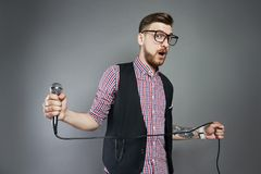 Karaoke man sings the song to microphone, singer with beard on g. Rey background. Funny man in glasses holding a microphone in his hand at the karaoke singer Stock Photography