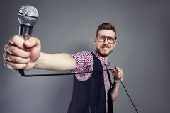 Karaoke man sings the song to microphone, singer with beard on grey background. Funny man in glasses holding a microphone. In his hand at the karaoke singer Stock Photos