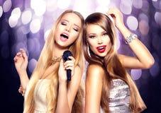 karaoke Meninas da beleza com um microfone Fotografia de Stock