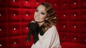 karaoke Muchacha de la belleza con un micrófono que canta y que baila sobre fondo rojo almacen de video