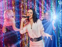 Karaoke party. Beautiful girl with a microphone having fun with her friends and singing Royalty Free Stock Photos