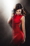 Karaoke Party. Beautiful Singing Girl. Woman in red with Microphone. Glamor fashion Woman in red dress with Microphone sing in karaoke at the night club Royalty Free Stock Photos