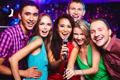 Karaoke party. Portrait of happy girls and guys singing in microphone in the karaoke bar Royalty Free Stock Image