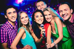 Karaoke party. Portrait of happy girls and guys singing in microphone in the karaoke bar Royalty Free Stock Photo