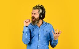 Karaoke. singing and dancing. Enjoying his favorite music. Man listening music with his headphones. bearded man hipster