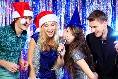 Karaoke song. Group of cheerful young people celebrating Christmas at the nightclub Stock Photos