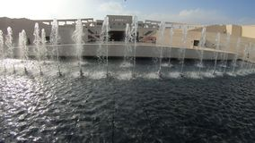 Karara Amphitheater fountains. Fountains with Katara Amphitheater at classical Greek theater in blurred background. Katara Village also named valley of cultures stock video