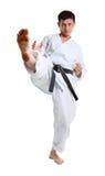 Karatè. L'uomo in un kimono colpisce il piede Immagine Stock
