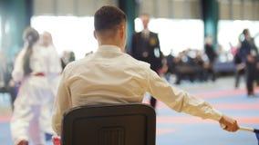 Karaté de concours d'art martial - jugez les entraîneurs regardant le combat femelle de karaté du ` s d'adolescent banque de vidéos