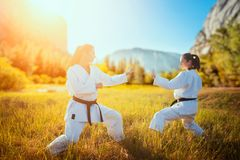Karaté de duas fêmeas na habilidade do combate do treinamento do quimono fotografia de stock